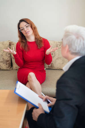 Desperate woman at a psychotherapy session. Male psychotherapist talking to a female patient with depression and neurosis. Psychological problems. Mature man with a patient.