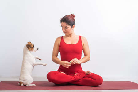 Caucasian woman in red jumpsuit sits in lotus position next to the dog. Yoga with a pet