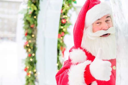 Santa claus peeks out of Christmas decorations outdoors