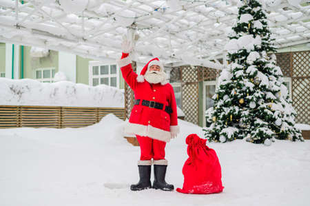 Portrait of santa claus by the christmas tree outdoors