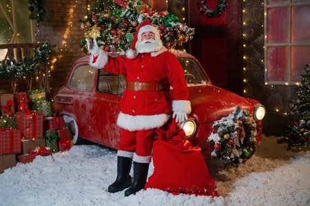 Santa Claus poses near a red classic car. Merry Christmas 版權商用圖片