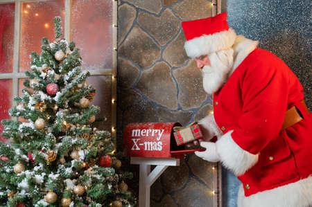 Santa Claus puts a gift in the mailbox. Christmas miracle 版權商用圖片