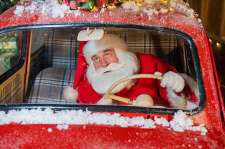 Portrait of Santa Claus driving a red car and delivering gifts for Christmas Stock Photo