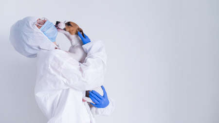 A woman in a protective suit and mask is holding a Jack Russell Terrier dog on a white background 版權商用圖片