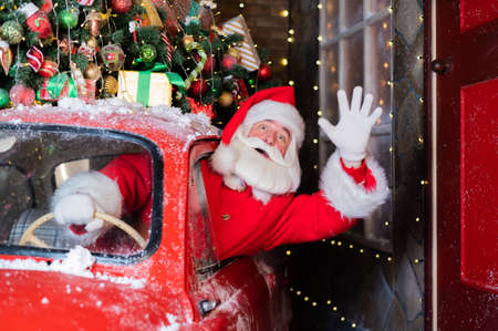 Santa claus greeting while driving a red retro car. Merry Christmas
