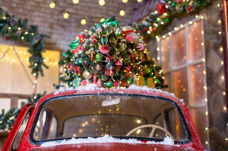Christmas tree on a red classic car outdoors. Decorated santa claus car