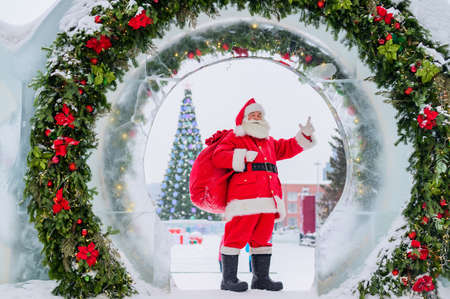 Santa Claus posing with a bag of gifts on the background of Christmas decorations outdoors 版權商用圖片