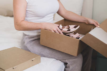 Happy woman unpacks online shopping for shoes. The girl received the package and opens it while sitting in the bedroom 版權商用圖片