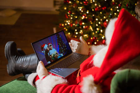 Happy mom and son talking to santa claus by video chat on a laptop. Woman and boy remotely wishes Merry Christmas