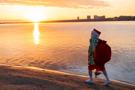 Santa claus in shorts and a shirt walks along the beach at sunset. Christmas in a hot country