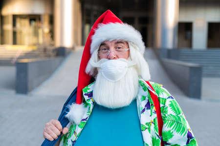 Portrait of santa claus in protective mask hawaiian shirt outdoors. Christmas in the coronavirus 版權商用圖片