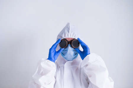 Woman doctor in a protective suit holds on to glasses