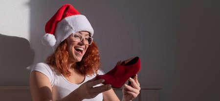 An excited woman in a Santa Claus hat takes red shoes from a cardboard box. The girl unpacks the delivered order for Christmas. Online shopping at home