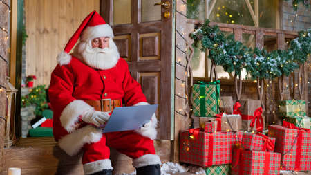 Santa Claus is sitting on the porch of the house and uses a laptop. Christmas concept