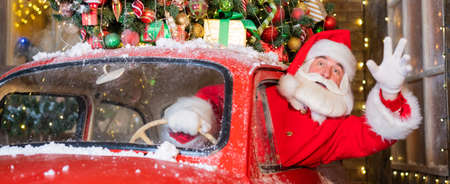 Santa claus greeting while driving a red retro car. Merry Christmas. Widescreen.