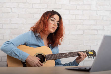 Young woman learns to play the guitar by video on a laptop. Online music lessons