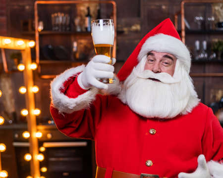 Santa claus with a glass of light beer wishes merry christmas and says toast 版權商用圖片