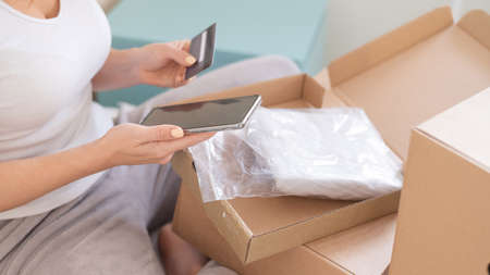 Online shopping using the application on the phone. A faceless woman sits in bed unpacks an order and holds a smartphone and a credit card. 版權商用圖片