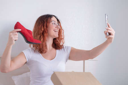 Caucasian woman sitting in bed and taking a selfie with a delivered purchase. Online shopping for shoes
