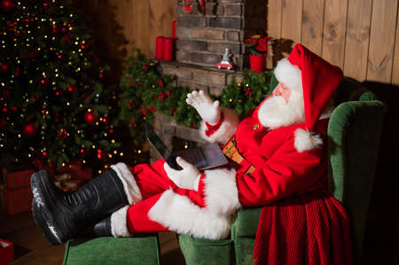 Happy santa claus sits at home in an armchair and remotely wishes merry christmas via video chat on a laptop 版權商用圖片