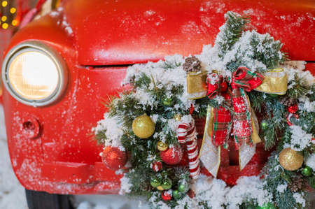 Christmas decorations on a red classic car outdoors. Santa claus car