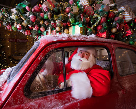 Portrait of santa claus driving a car loaded with a Christmas tree and gifts