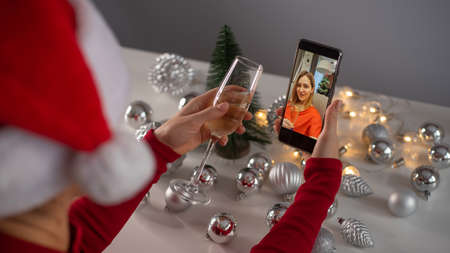 Women make a video call on a mobile phone. Girls drink champagne celebrate Christmas and communicate remotely by smartphone