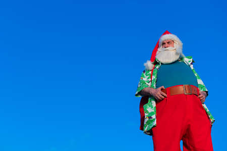 Santa claus in a hawaiian shirt on a blue background.