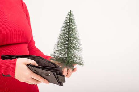A woman is holding an empty purse next to a small artificial Christmas tree. The financial crisis during the holidays