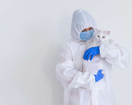 A woman in a protective suit with gloves and a mask is holding a white cat. Doctor tests pets for coronavirus