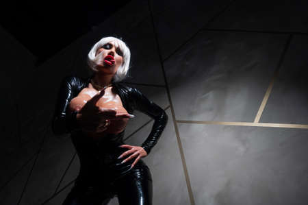 Sexy woman in a blonde wig and latex catsuit. Girl with big fake