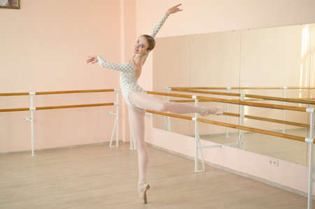 Beautiful ballerina in body and white tutu is training in a dance class. Young flexible dancer posing in pointe shoes. Stock Photo