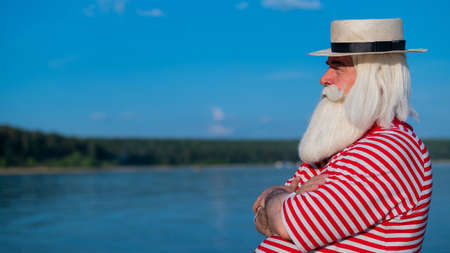 Elderly gray-haired man with a beard in a striped bathing suit and hat posing on the beach. Senior citizen on vacation by the lake.