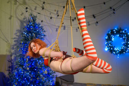 A girl in red underwear and striped stockings, tied with a rope in the Japanese style of shibari, weighs suspended. Bdsm. Standard-Bild