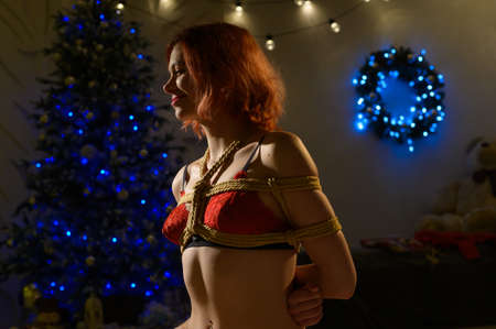 The red-haired girl is tied with a rope using the Japanese shibari technique. Woman in red underwear near a New Year tree Stock Photo