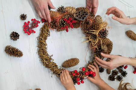 Girls helps her grandmother to make a wreath for Christmas with her own hands. Close-up of hands of a woman and a child making decorations from fir branches, cones and rowan