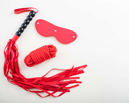 BDSM set on a white background. Leather red eye mask rope and whip. Copy space 写真素材