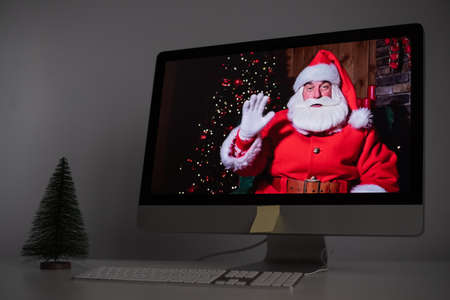 Santa Claus remotely wishes Merry Christmas via a video call on the computer. A man dressed as Santa Claus on a monitor. 2021 new year concept