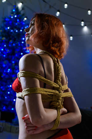 The red-haired girl is tied with a rope using the Japanese shibari technique. Woman in red underwear near a New Year tree