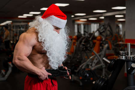 Man in santa claus hat and naked torso posing in the gym.