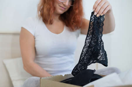 An excited woman unpacks a delivered order. Online shopping for lingerie at home