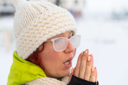 Portrait of a woman in glasses covered with hoarfrost. The girl is freezing and forgot gloves in very cold weather and blows on her hands
