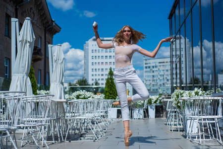 A beautiful ballerina is dancing outdoors on a warm summer day. Young woman in pointe shoes.