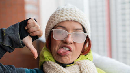 A disgruntled Caucasian woman stands on the balcony of a brick house in winter, showing her tongue and thumb down. Girl in ice-covered glasses on the street outdoors Imagens