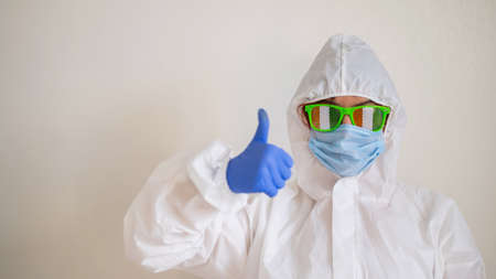 A woman in a protective suit and a medical mask and wearing funny glasses celebrates st patricks day and shows a thumb up