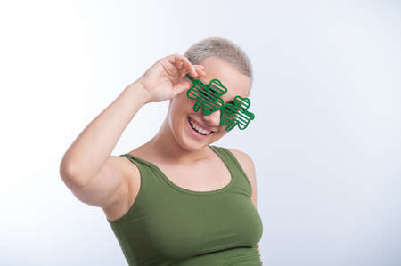 Portrait of a young Caucasian woman with a mans haircut in a green T-shirt and cheerful glasses on a white background. The girl celebrates st patricks day