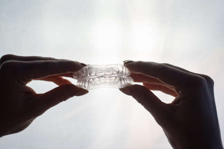 Transparent trays for correcting teeth in female hands. Removable plastic retainers