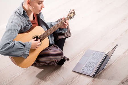 Young hipster woman watching guitar tutorials on laptop. Distance learning music