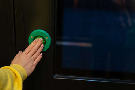 Button for opening doors on the train. Close-up of female hands on the green automatic door opener button