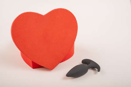 Heart-shaped box and butt plug on a white background. Love on February 14. Banque d'images